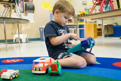 Photograph of boy playing with toy trucks - credit: Kristin Beadle